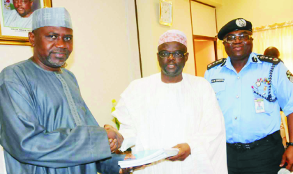 Inspector-General of Police, Mr Ogbonna Onovo (right) watching as the Permanent Secretary, Ministry of Police Affairs, Alhaji Bukar Goni-Aji (left) receives hand over note from out-going Minister of Police Affairs, Dr Ibrahim Lame, in Abuja, last Friday.