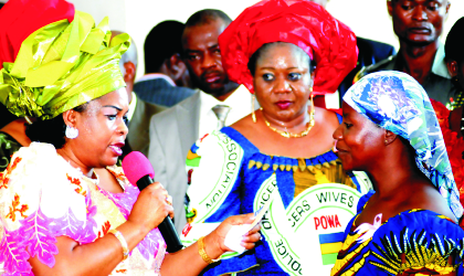 Wife of the Acting President, Mrs Patience Goodluck Jonathan, presenting a cheque to Mrs Martha Usman, member, Police Wives Association (PWA),at the seminar on Enhancing the Economic and Health Status of Police Families and  Disbursement of Loans by  NPF Micro Finance to POWA/PWA members in Abuja. With them is wife of AIG Zone 6, Mrs Filomina Ogboudu, last Monday.