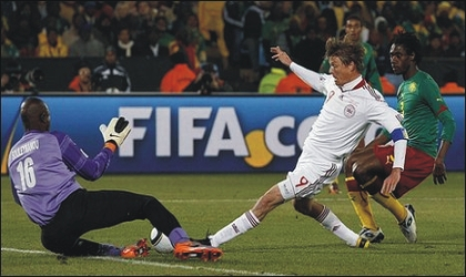 Denmark's Jon Dahl Tomasson (9) trying to beat Cameroon's keeper, yesterday.