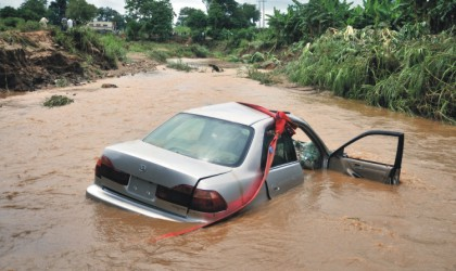 One of the two cars swept off the bridge at the Old Karmo River due to heavy down pour in Abuja, yesterday. Four occupants of the vehicles were confirmed dead.
