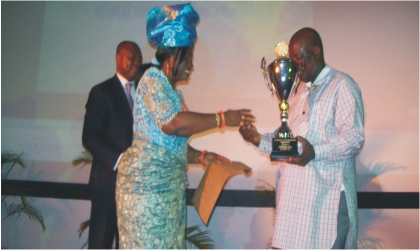 Mrs Josephine Diete-Spiff on behalf of her husband presenting the best performing local government  trophy to Chairman, Gokana Local Government Area, Mr Victor Giadom at the Rivers State House of Assembly Auditorium, yesterday.