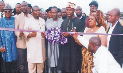 Governor of Rivers State, represented by state Commissioner for Works, Hon Dakuku Peterside (middle) being assisted by Deputy Speaker, Rivers State House of Assembly, Hon Dumnamene Deekor (3rd left) and Hon Maureen Tamuno, while cutting the tape during the commissioning of Tamuno's constituency project in Ogu/Bolo LGA, on Tuesday.