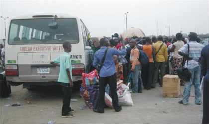 Passengers struggling to board a bus at Mile I Motorpark in Port Harcourt on Christmas Day.