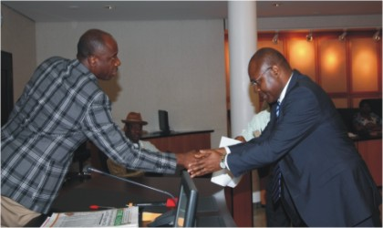 Rivers State Governor, Rt. Hon. Chibuike Rotimi Amaechi (left) congratulating Dr Tekena Ibanibo after being sworn-in as Permanent Secretary in the State Civil Service at Government House, Port Harcourt, yesterday.