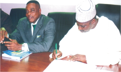 Chairman, Rivers State Independent Electoral Commission, Prof Nimi Briggs (left) watching as Director-General, National Institute of Policy and Strategic Studies, Kuru, Jos, Prof Tijani Bande signs the visitors notebook, when members of the Institute visited RSIEC, yesterday. Photo: Chris Monyanaga
