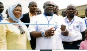 General Overseer, Omega Power Ministries, Apostle Chibuzor Chinyere (middle), cutting the tape to officially commission the Church's free nursery and primary school buildings at the OPM headquarters in Port Harcourt. With him are Pastor Godwin Ozoemelam (right), Director of Welfare, Mrs Maureen Chikwu  and others, yesterday.