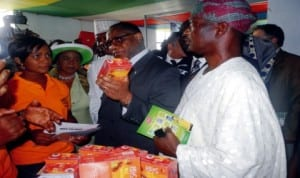 Minister of Trade and Investment, Dr Olusegun Aganga (middle), inspecting a product at one of the exhibition stands, during the opening ceremony of Lagos International Trade Fair in Lagos,  last Friday. With him is the representative of the Governor, Mr Wale Raji (right).