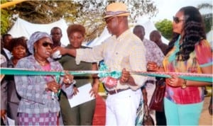 Representative of the wife of Rivers State Governor, and Commissioner for Women Affairs, Mrs Joeba West (left) cutting the tape with the assistance of her Commerce and Industry counterpart, Barr Chuma Chinye, at the opening of the 3rd Port Harcourt Xmas Discount Market in Port Harcourt , yesterday. Photo: Chris Monyanaga