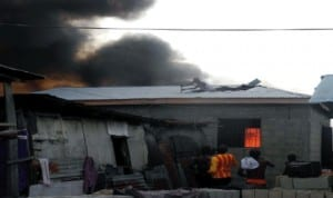 Some houses gutted by fire at Sari Iganmu in Lagos last Wednesday, on the roof as a man removing roofing sheets from a near by house during the fire incident recently.