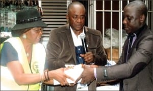 Rivers State Permanent Secretary, Ministry of Special Duties, Dame Mina Benebo (left), presenting some fire safety documents to Chairman, Mile One Market Traders Association, Deacon Keneth Eze (right), during a public sensitisation programme on fire safety and prevention to markets and parks organised by the Ministry in Port Harcourt last Wednesday. With them  is  Commissioner for Special Duties, Barrister Dickson Omunakwe.