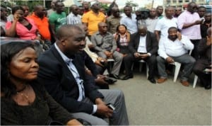 Rivers State legislators sitting outside the House of Assembly Complex.