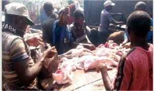 Men processing chicken for Christmas at Wuse Market in Abuja, yesterday.