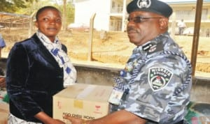 Representative of IGP, Mr Chris Olakpe (right), presenting food items on behalf of IGP to one of the widows of police officers that lost their lives on duty, Mrs Nandi Peter, during the presentation of food items to the widows in Jos last Monday.