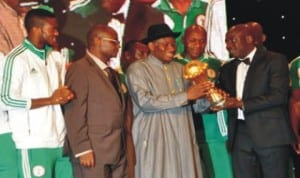 President Goodluck Jonathan (3rd left) receiving the 2013 AFCON trophy from Minister of Sports Malam Bolaji Abduallahi after the Eagles trumph in South Africa in February
