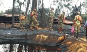 Securitymen supervising the destruction of illegal oil refineries at Alakiri in Okirika Local Government Area, of Rivers State last Thursday