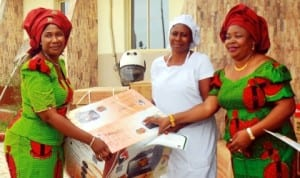 Coordinator,  Nigerian Army Officers'  Wives Association (NAOWA), 2 Brigade , Port Harcourt, Mrs Adesuwa Uzamere (left),  presenting a Starter Pack to a beneficiary, while one of the NAOWA officials watch, at the graduation of NAOWA vocational skills acquisition trainees at Bori Camp, Port Harcourt last Friday.