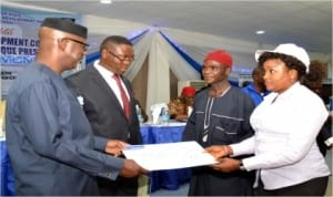 Cross River State Governor, Senator Liyel Imoke (left), presenting a cheque to one of the beneficiary communities of the N470million development grant while the DG of CRSDA, Pastor Ovat (2nd left),  watches in Calabar, recently.