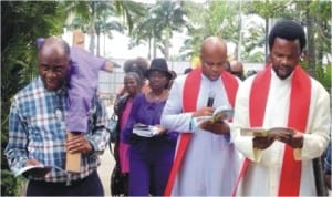 Rivers State Governor, Chibuike Amaechi (left with a cross) participating in Good Friday Stations of the Cross. The hooded cross on his left shoulder is symbolic.