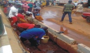 People scooping kerosene from the drainage at the scene of a tanker accident at Uselu in Benin-City, recently. Photo: NAN