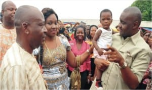 Sen. Magnus Abe with a little baby (right), his wife Bariyaah (centre) and Chairman, Khana LGA, Gregory Nwidam during the presentation of wrappers to 1,900 women in Bori, recently.