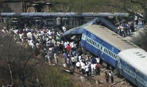 People gather around a derailed passenger train in India