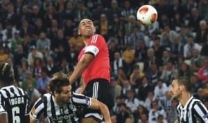 Benfica's captain, Luisao in aerial contest with Juventus players during the semi-final stage of the UEFA Europa Cup in Turin, Italy