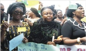 Minister of State for Foreign Affairs 1, Prof. Viola Onwuliri (left), holding a lighted candle symbolising the light that will drive away darkness in Nigeria during a protest over abducted Chibok School Girls in Owerri On Tuesday.