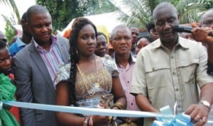 Senator Magnus Abe flanked by his wife, Bariyaah and Chairman, Gokana Local Gov't Council, Ledee Demua (1st left), cutting the tape to inaugurate a Neighbourhood Water Scheme in Giokoo Community of Rivers State, recently. Photo: NAN