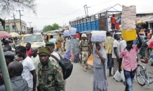 People doing  Business  under the protection of soldiers in Maiduguri last Saturday. Photo: NAN
