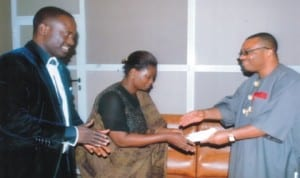 General Manager, Rivers State Newspaper Corporation (RSNC), Mr Celestine Ogolo(right), presenting a souvenir on behalf of Wisdom to Wealth and Development Foundation to the beneficiary of the initiative, Mrs Gloria West, during a courtesy visit to the corporation. With them is Niger Delta Coordinator, Wisdom to Wealth and Development Foundation, Prince Anyanate Kio, yesterday. Photo: Egberi A. Samspson