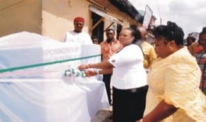 Wife of former member of Rivers State House of Assembly, Mrs Oroma Nmerukini (middle) cutting a tape to commission a water project   initiated by a federal lawmaker in Mile 1, Rumuwoji community, Port Harcourt, recently.  With her is the initiator of the project and member, House of Representatives, Mrs Blessing Boma Nsiegbe
