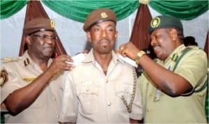 L-R: Comptroller, Nigeria Immigration Service, Rivers Command, Mr Mike Longe (left) and Controller of Prisons, Rivers Command, Mr Patrick Ondoma (right) decorating Mr Vincent Ekoko with his new rank,  during decoration of newly promoted officers of Immigration Service in Port Harcourt, last Friday