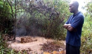 A youth leader in Kalaba community, Mr Samuel Oburo, at the oil spill site within an oil field in Kalaba community, Yenagoa Local Government Area of Bayelsa State, recently.