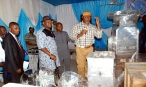 Rivers State Deputy  Governor, Engr. Tele Ikuru (centre) listens as Commissioner for Commerce and Industry, Barr. Chuma Chinye, explains functions of some equipment for distribution to beneficiaries