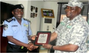 AIG Zone 2 Command, Mamman Tsafe (left), presenting a plaque to the Customs Controller, Federal Operation Unit, Zone A, Mr Turaki Umar, during the Custom's boss familiarisation visit to the AIG's office in Lagos, recently.