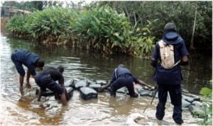Officers of Nigeria Security and Civil Defence Corps (NSCDC) recovering jerry cans used in siphoning petrol from pipe lines at Oke Isawo in Ikorodu, Lagos State, last Friday