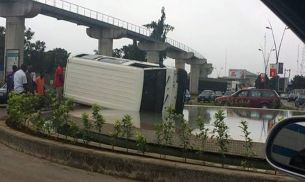 A speeding driver bus yesterday lost control and veered into a water fountain at Government House, Port Harcourt entrance. Picture shows bewildered passers-bye watching the up-turned bus inside the fountain
