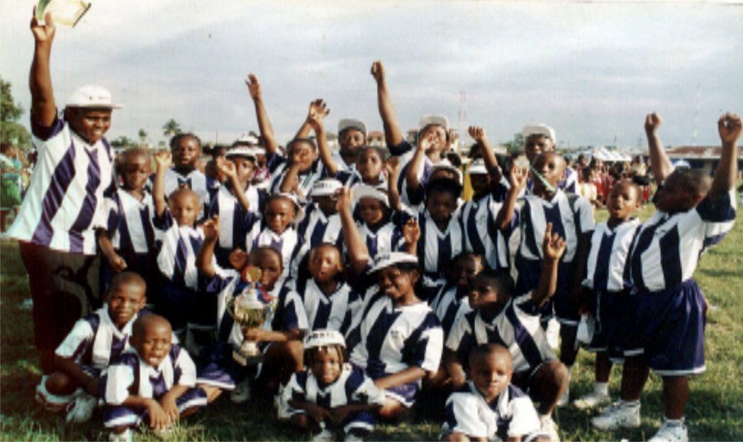 Secondary school children celebrating with their trophy after schools competitions.