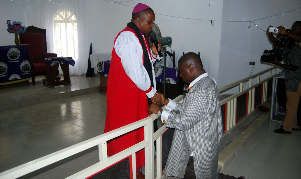 Dr. Dakuku Peterside, APC governorship candidate in Rivers State receiving blessing from Bishop Solomon S. Gberegbara (left)