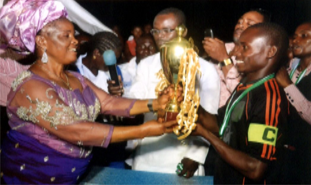 Cup Donor, Hon Felicia Tanen (left) presenting the winners trophy to DCAT FC captain at the end of the 2014 Botem Football tournament in Tai LGA, Rivers State. Photo: Chris Monyanaga