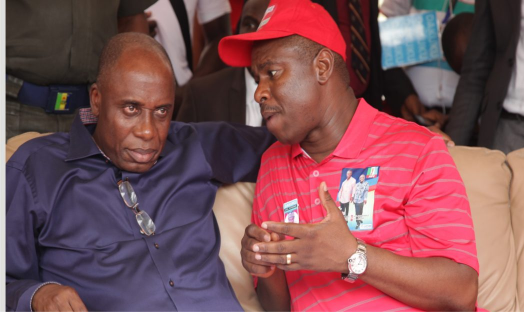 Rivers State Governor, Rt Hon Chibuike Amaechi, (left) listening to an explanation by APC Governorship candidate, Dr Dakuku Peterside, during APC rally at Etche, yesterday.