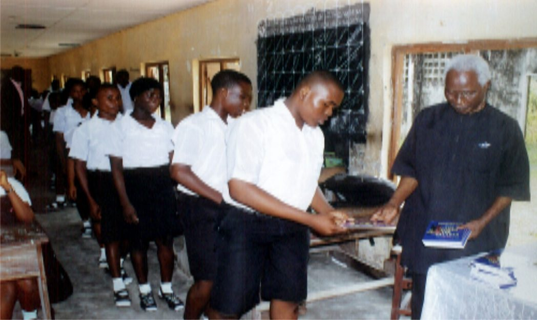 Dr Elechi Amadi (right) presenting some copies of Free Books commissioned by Rivers State Government to students from Comprehensive Secondary School, Opobo community, in Rivers State.Photo: Egberi A. Sampson