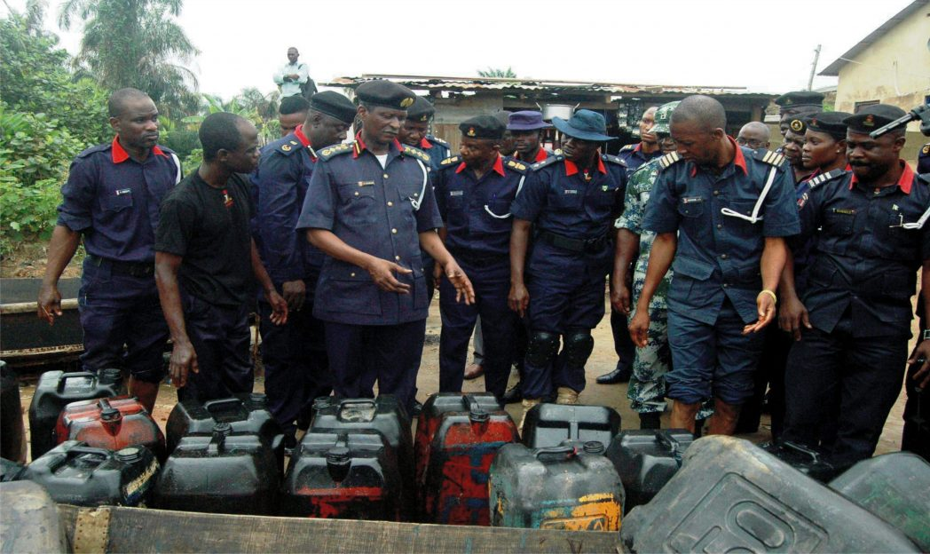 Commander General of Nscdc, Dr Ade Abolurin (3rd left),  inspecting seized jerry cans of petrol from vandals during his tour of Oke-oko Isawo in Ikorodu, recently.