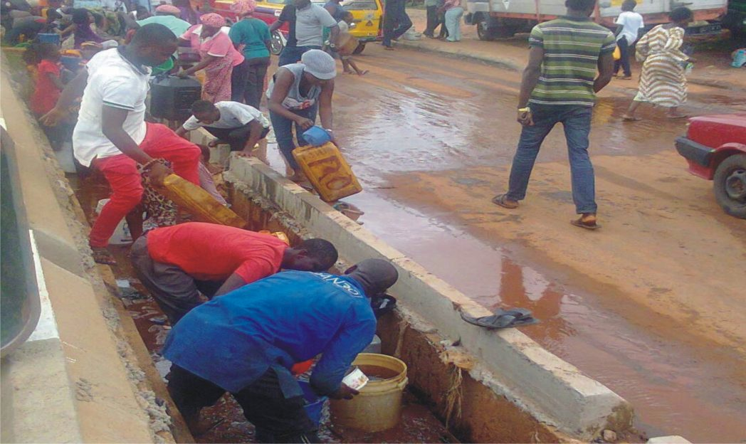 People scooping kerosene from the drainage at the scene of a tanker accident at Uselu in Benin-City.