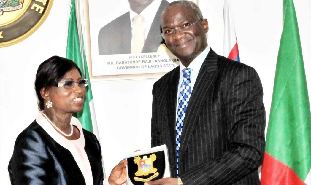 Lagos State Governor, Babatunde Fashola (right),  presenting a plaque to  the President, Governing Council of Institute of Directors, Mrs  Eniola Fadayomi,  during a visit of the  governing council to Governor  Fashola in Lagos last Monday