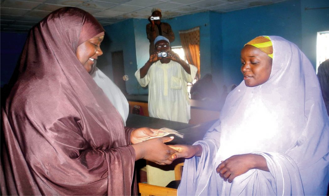 Wife of Dandume Local Government Chairman, Hajia Hadiza Ya'u Ahmad-noa (left), presenting cash empowerment support to one of the 50 physically challenged persons in Dandume, Katsina State recently.