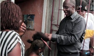 Leading by example: Rivers State Governor, Rt. Hon. Chibuike Rotimi Amaechi plaiting the hair of a woman as he convinces her to vote for the All Progressives Congress (APC), during his door to door campaign in Bonny Island, Rivers State, Wednesday.