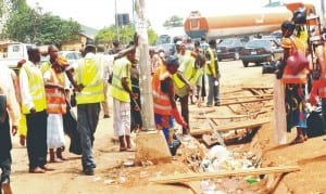 Environmental sanitation workers cleaning the scene of the Nyanya explosion in Abuja recently.