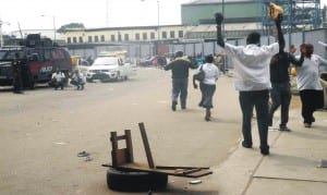 People rasing their hands in compliance with police order as they walk pass the scene of  a renewed clash between members of National Union of Road Transport Workers at Oshodi, in Lagos, recently.