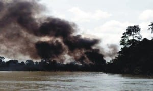 Thick smoke blowing from a burning vessel, following an operation of the Joint Task Force (JTF) agianst oil thieves in which boats and illegal refinery site at Ogboinbiri Community, Southern Ijaw Local Government Area of Bayelsa State were reportedly set ablaze, recently.           Photo: NAN